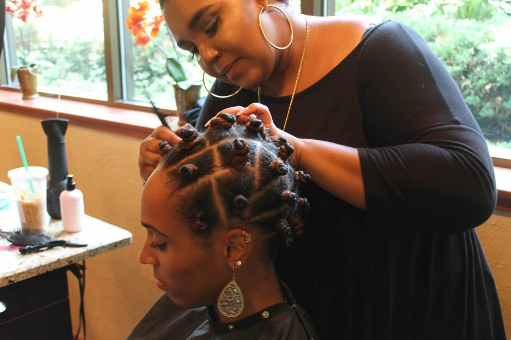 Brittany performing a curly hair demo at Curls Night Out